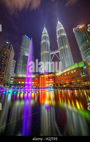Suria KLCC Shopping Mall and the Petronas Twin Towers night colorful water show. - Stock Photo