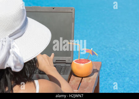 Rear view of a woman using laptop at the poolside. Grapefruit with paper parasol and drinking straw on the table, - Stock Photo