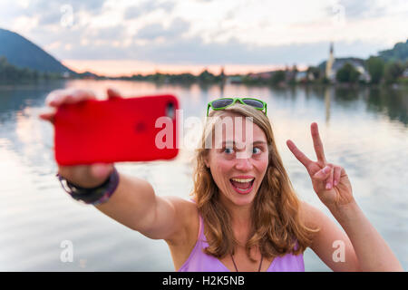 Young woman taking selfie, laughing and making peace sign, Schliersee, Upper Bavaria, Bavaria, Germany - Stock Photo