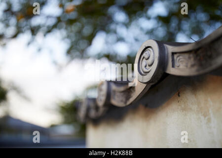 A detail shot of the edge of a Japanese ceramic roof tile on an old wall with a soft blurred background sky and - Stock Photo