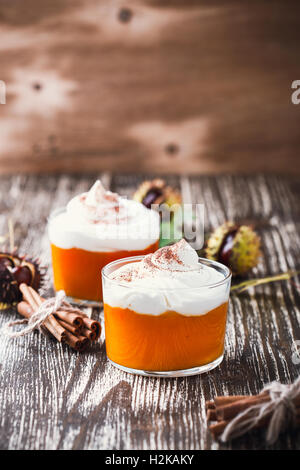 Homemade autumn dessert of pumpkin mousse with whipped cream on wooden rustic table against background of chestnuts - Stock Photo