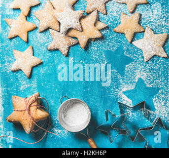 Christmas or New Year holiday food background. Sweet gingerbread cookies in shape of star with sugar powder on bright - Stock Photo