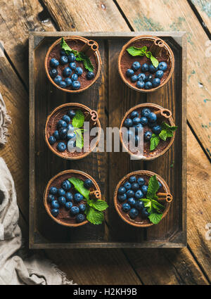 Homemade Tiramisu dessert in glasses with cinnamon sticks, mint leaves and fresh blueberries served in wooden tray - Stock Photo