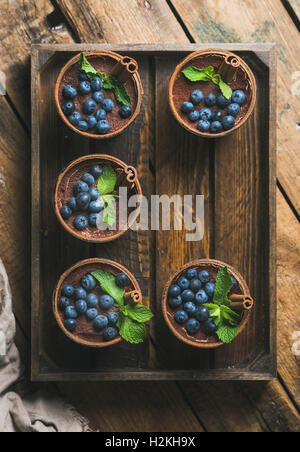 Homemade Tiramisu dessert in glasses with cinnamon sticks, mint leaves and fresh blueberries in wooden tray over - Stock Photo