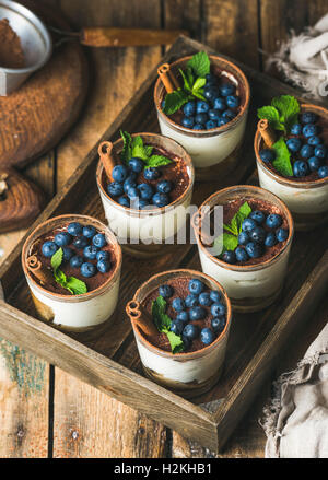 Homemade Tiramisu dessert in glasses with cinnamon, mint and fresh blueberry in wooden tray over rustic wooden background, - Stock Photo