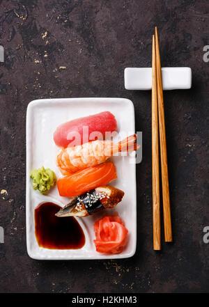 Nigiri sushi set on white plate on dark background - Stock Photo