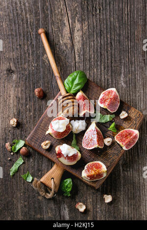 Fresh sliced figs with ricotta cheese, basil leaves, hazelnut and honey from honey dipper on small wood cutting - Stock Photo