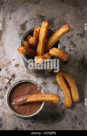 Traditional spanish treat churros with chocolate sauce, served in tin can over old textural metal background. Top - Stock Photo