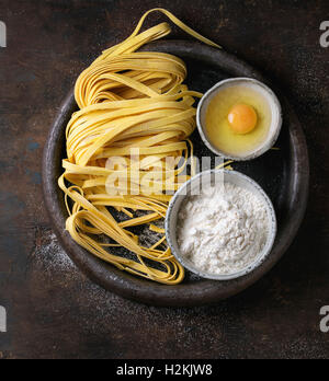 Raw uncooked homemade italian pasta tagliatelle with pasta cutter, bowls with white flour and broken egg in old - Stock Photo