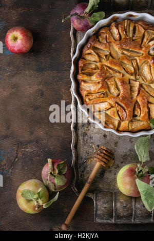 Homemade apple cake pie in white ceramic form on vintage metal tray with fresh apples with leaves and honey over - Stock Photo