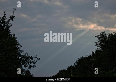 Bright rays of sun bursting through dark clouds - Stock Photo