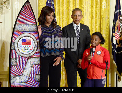 Washington, Us. 29th Sep, 2016. American Gold Medal-winning gymnast Simone Biles, right, presents an autographed - Stock Photo