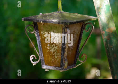 a vintage style street light with crown on the top. Beautiful historical retro metal Streetlight on green tree background. - Stock Photo