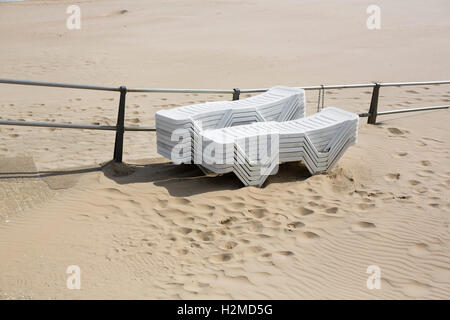 White plasrtic sun loungers sitting in the sand on an empty beach. - Stock Photo