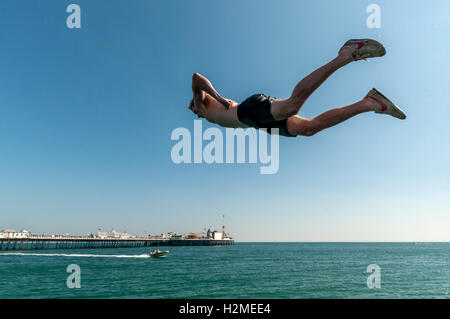 Young people jumping into the sea from the Banjo Groyne on Brighton beach - Stock Photo