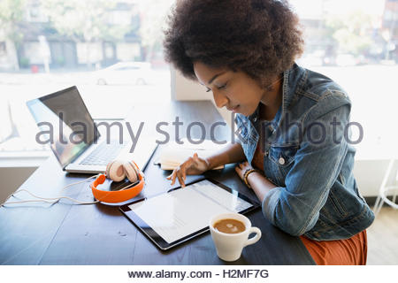 Focused woman working at digital tablet in cafe - Stock Photo
