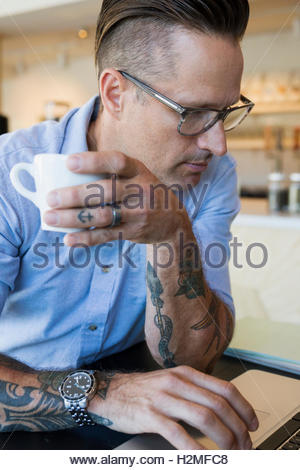 Close up man with tattoos drinking coffee at cafe - Stock Photo