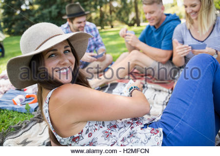 Portrait smiling woman playing cards with friends in summer park - Stock Photo