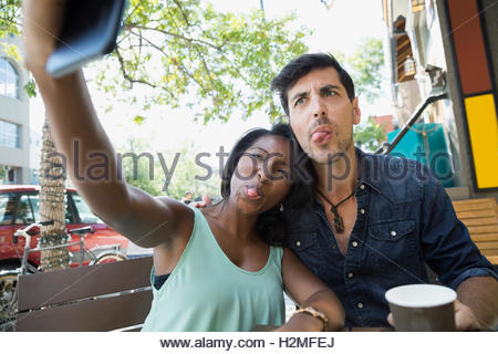 Playful couple making silly faces and taking selfie with camera phone at sidewalk cafe - Stock Photo