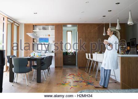 Woman in bathrobe drinking coffee in kitchen - Stock Photo