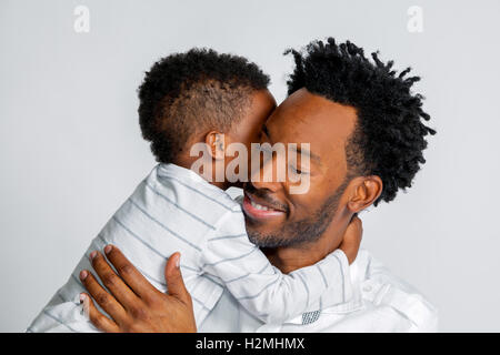 A young African American son hugs his father around the neck.  They are both dressed in white against a white background. - Stock Photo