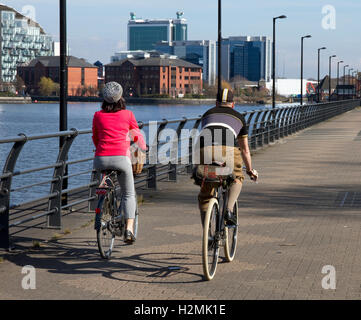 Cyclists ( vintage style) riding along Trafford Wharf , Salford Quays, Salford / Manchester, UK - Stock Photo