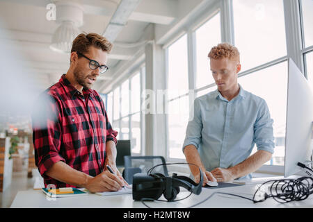 Two young businessman working together. They are standing at a table with virtual reality glasses. One using computer and other