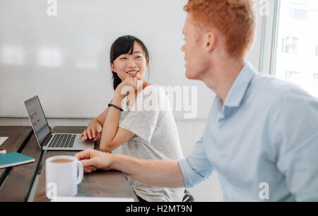 Two business people sitting at conference table and discussing during business meeting. Coworkers sitting in boardroom - Stock Photo