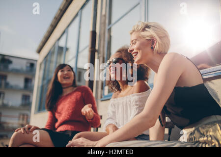 Group of female friends having fun while sitting at outdoor cafe. Three young women sitting in a terrace chatting - Stock Photo