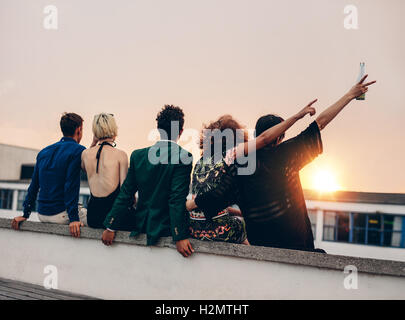 Group of friends partying on terrace with drinks. Young men and women enjoying drinks on rooftop at sunset. - Stock Photo