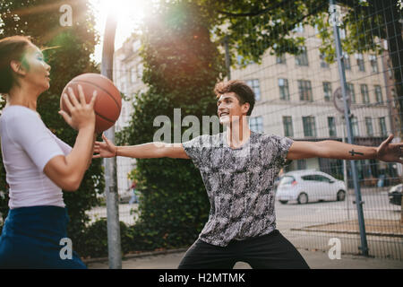 Two young man and woman playing streetball against each other. Teenage friends playing a game of basketball on an - Stock Photo