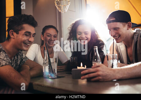Group of friends sitting together in a cafe looking at mobile phone and smiling. Young guy showing something to - Stock Photo