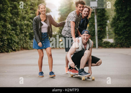 Full length shot of teenage guys on skateboard with girls. Diverse group of friends having fun outdoors. - Stock Photo