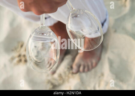 Closeup of two glasses in hand at man walking barefoot on the beach - Stock Photo