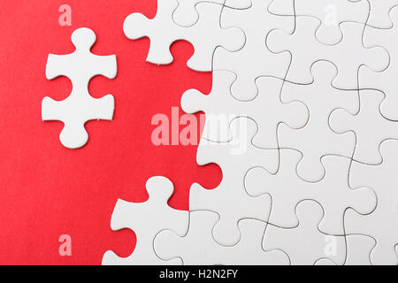 Incompleted white puzzle on red background - Stock Photo
