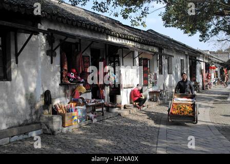 A fruit seller pushing his tangerine cart in Tongli, Jiangsu, China. - Stock Photo