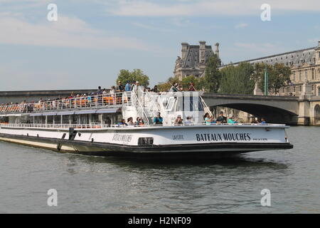 Tourists enjoying a sight seeing trip on a river cruise in the Seine in Paris - Stock Photo