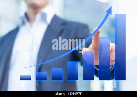 Business consultant presenting a blue chart about growing markets with office buildings in background - Stock Photo