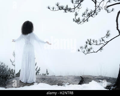 Woman in white dress standing on a cliff, meditating with spread hands, embracing the nature, spiritual concept - Stock Photo