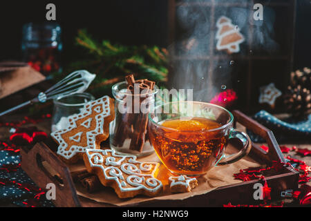 Christmas cookies with steaming cup of tea - Stock Photo