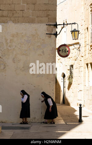 Two aged nuns taking a stroll in the ancient city of Mdina on the island of Malta - Stock Photo