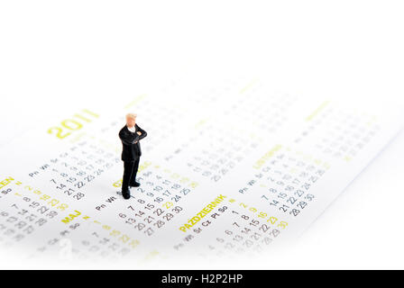miniature man on kalendar standing - Stock Photo