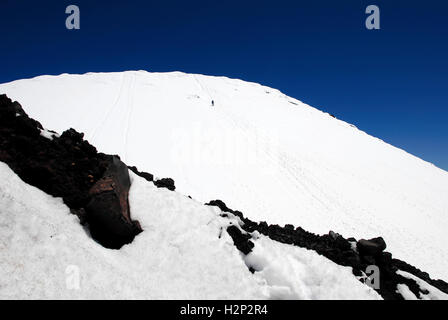 A lone hiker ascends the snow covered summit of Mount Ngauruhoe in Tongariro National Park, New Zealand. - Stock Photo