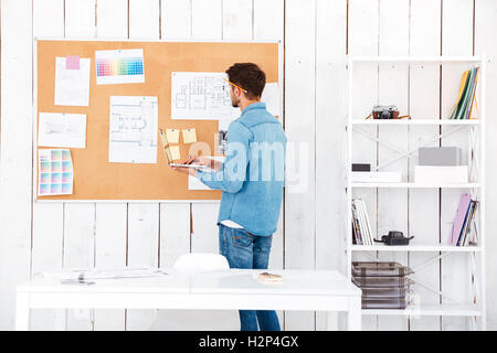 Back view of a concentrated young man looking at the task board and using laptop while standing in office - Stock Photo
