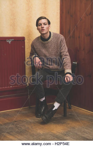 young guy hanging out in a social club wearing a knitted jumper, black jeans and doc martens, - Stock Photo