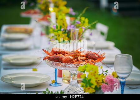 Crayfish in glass bowl on elegant garden party table - Stock Photo