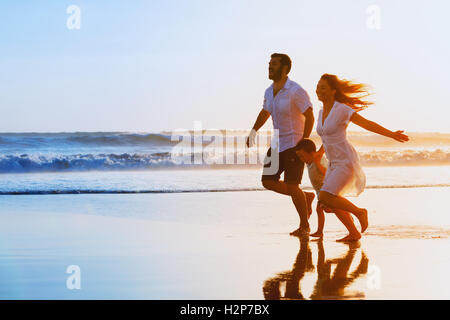Happy family - father, mother, baby son hold hands and run together with fun along sunset sea surf on black sand - Stock Photo