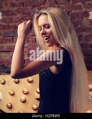 Happy dancing young woman singing the song on yellow star and bricks wall background. Toned closeup portrait - Stock Photo