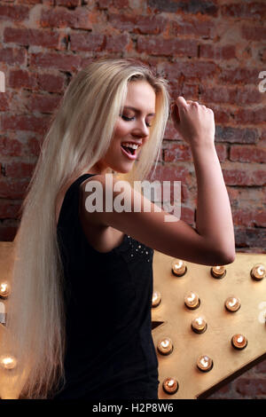 Happy dancing young woman singing the song on yellow star and bricks wall background - Stock Photo