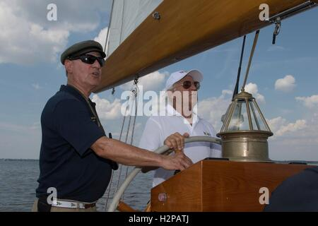 Singer Jimmy Buffett, right, tries his hand at the helm of the U.S. Naval Academy training sailboat Summerwind alongside - Stock Photo